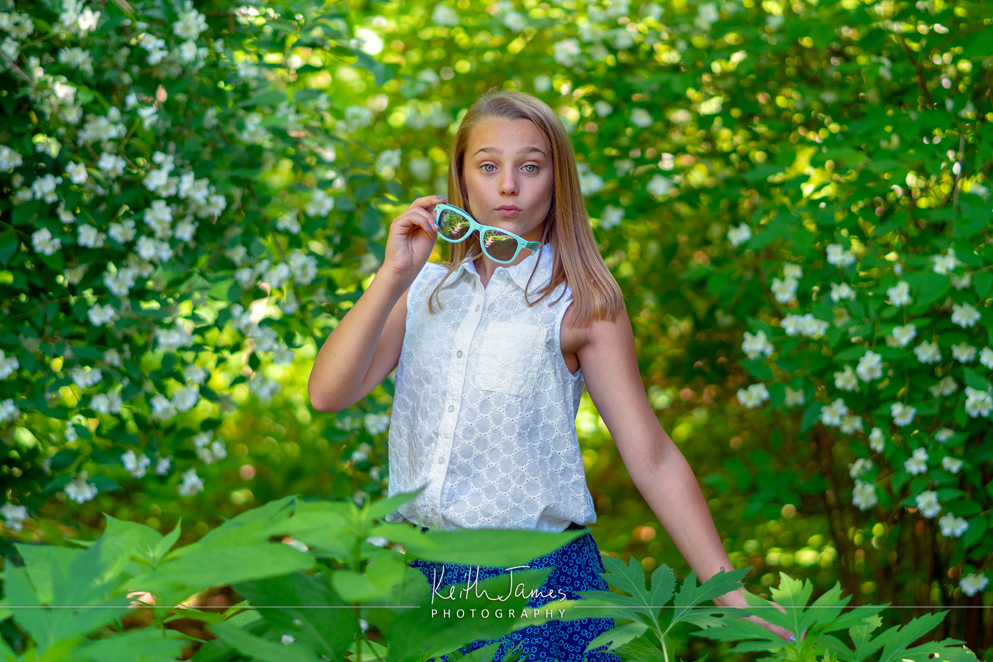 Portrait of a pre-teen girl against a backdrop of flowers.