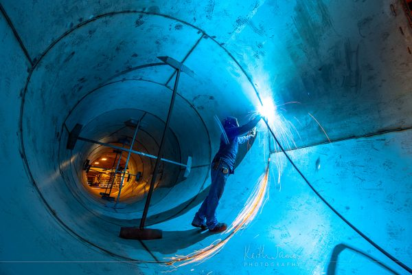 Workplace photography: A welder works on a 10-foot diameter stainless steel pipe