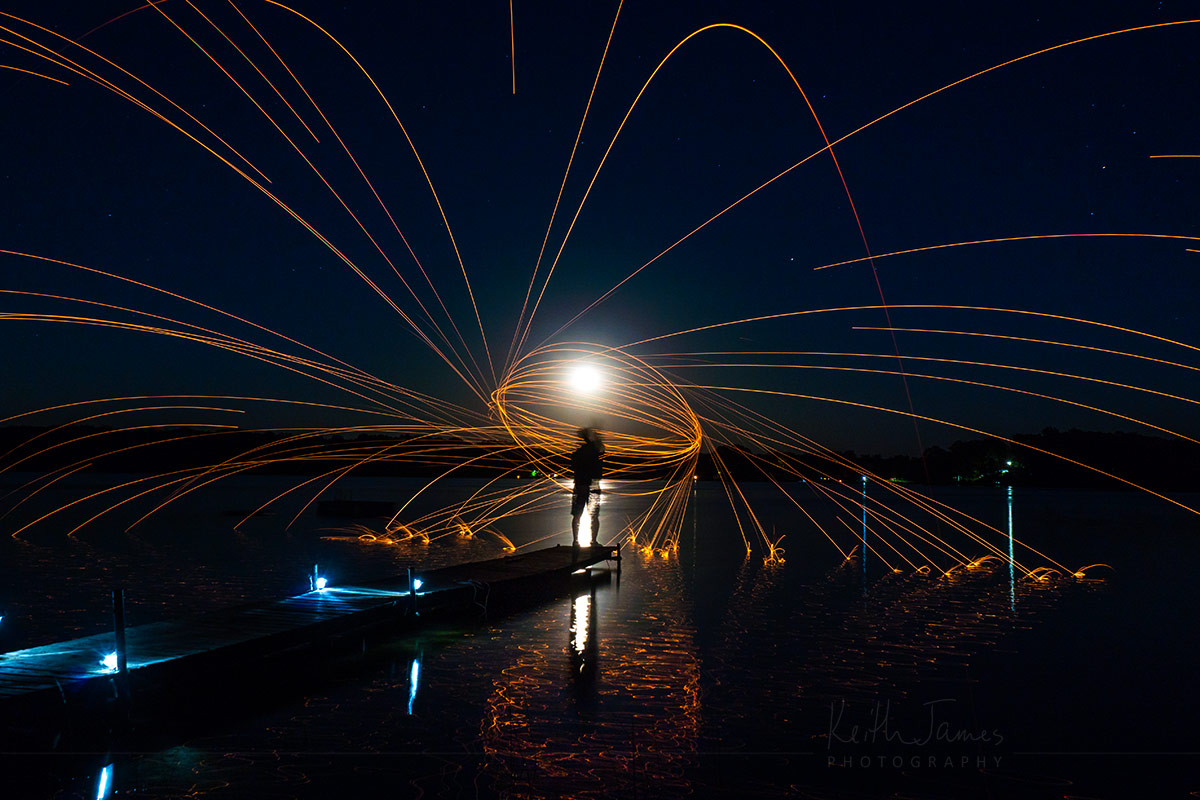Long Exposure: Flaming steel wool and wire whisk trick on a dock over water.
