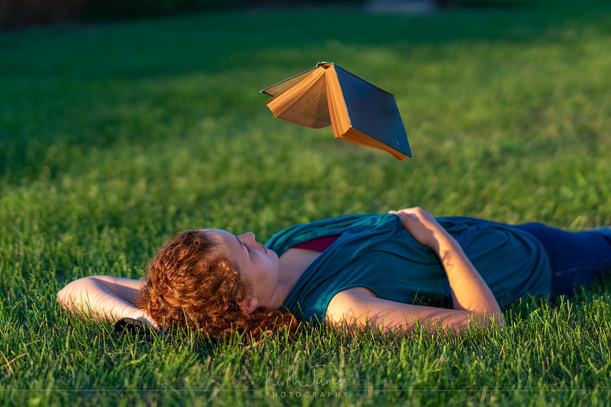 Levitation photography: A young woman lies on the grass reading while a book hovers over her.