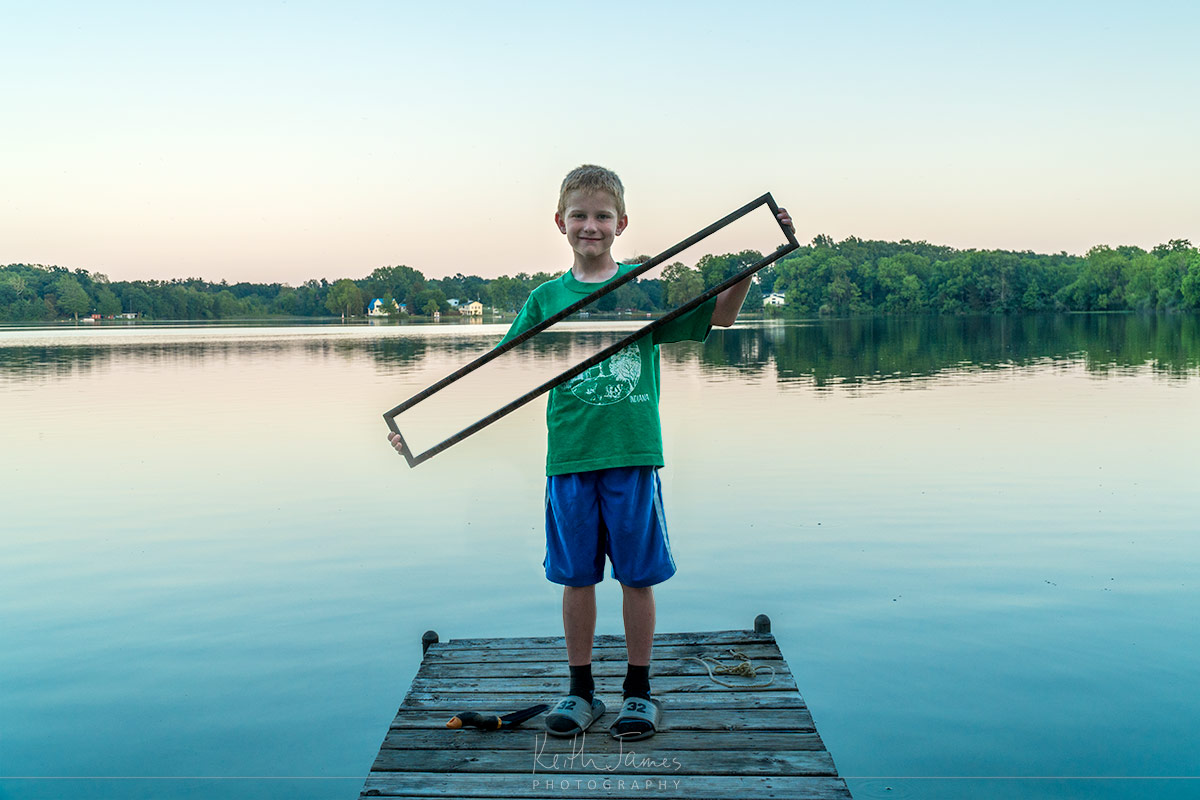 Trick photography: A young boy holds a mirror and you can see the lake right through him.