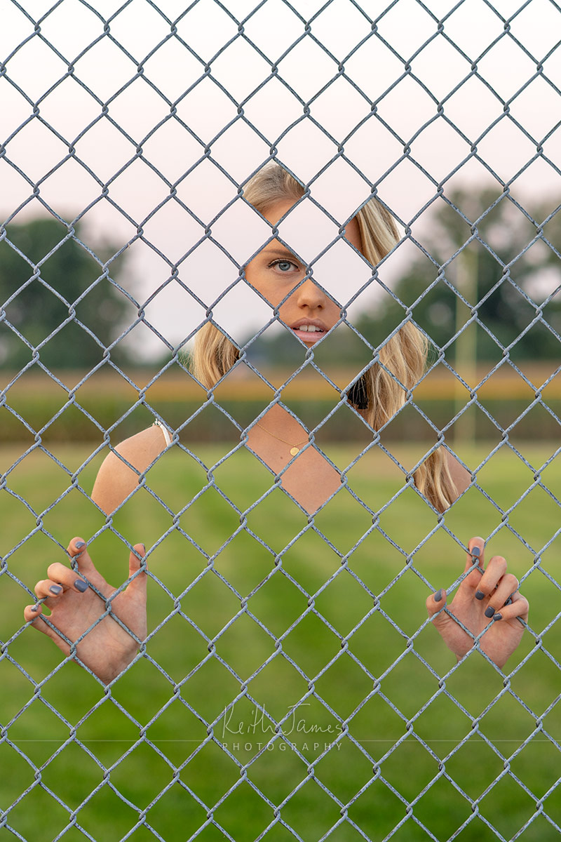 Trick photograph: young woman through a chain link fence.