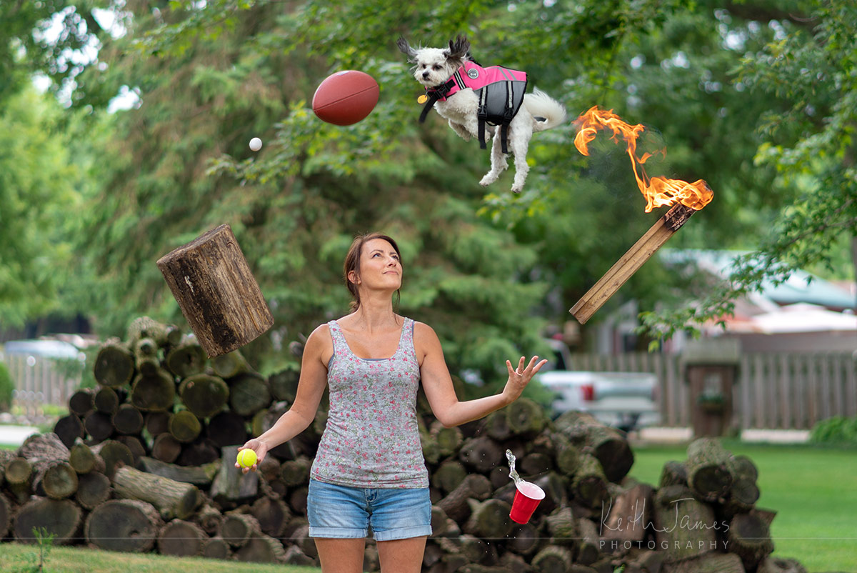 Trick photography: A woman juggles a tennis ball, wood log, egg, football, dog, flaming stick, and a cup of water.